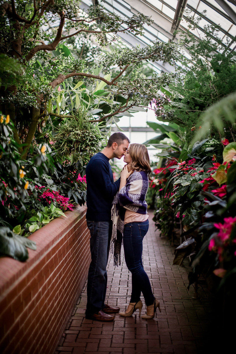 Standing in a greenhouse at the Biltmore while he pulls her in for a kiss by Knoxville Wedding Photographer, Amanda May Photos.