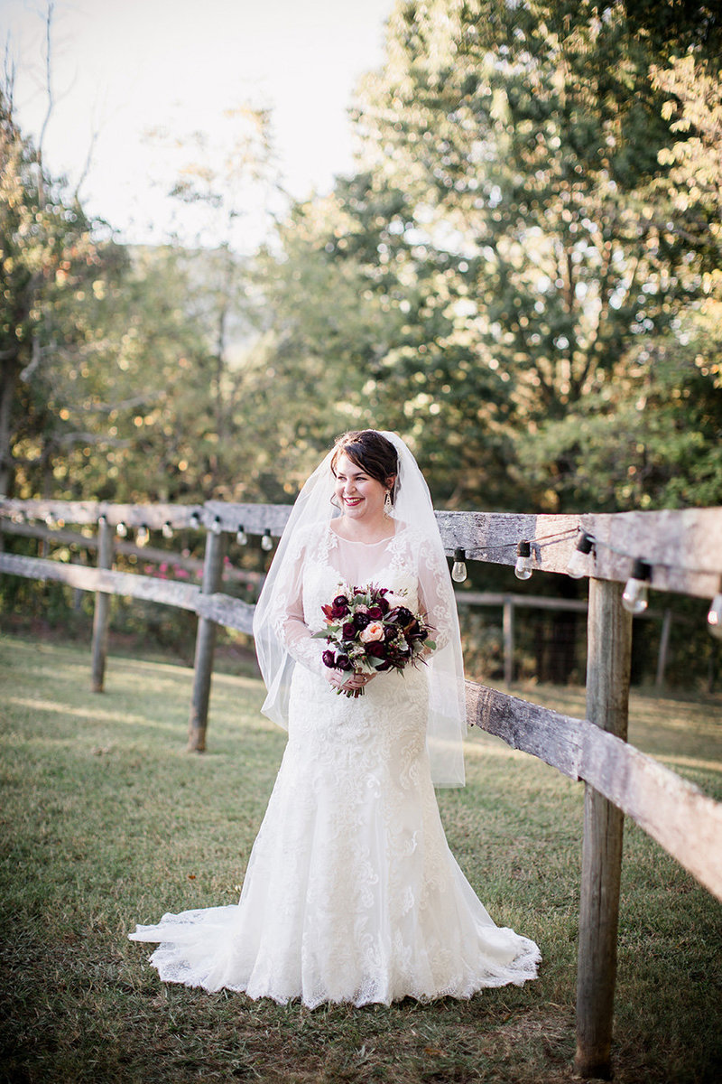 Bride standing along fence at the Barn at High Point Farms by Knoxville Wedding Photographer, Amanda May Photos.