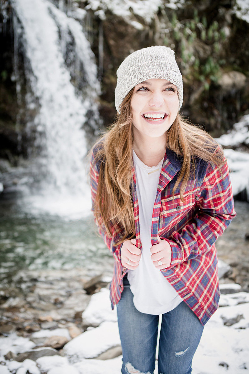 She holds onto her flannel and laughs hard with Grotto Falls behind her in the Smoky Mountains by Knoxville Wedding Photographer, Amanda May Photos.