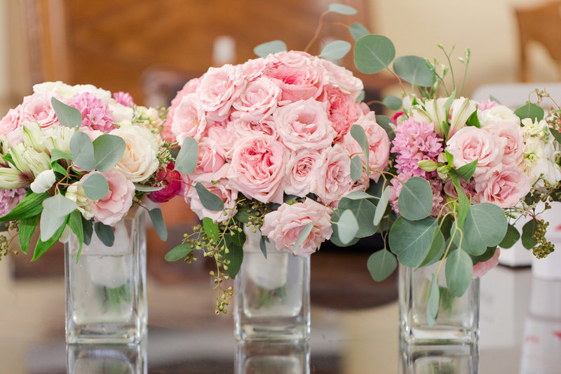 Pink peony bouquets lined up in vases