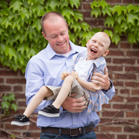 Mom writes wonderful review for photographers when her child with special needs is embraced by his dad in pure joy in this photo.