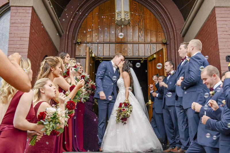 bride and groom kiss leaving church bridal party blows bubbles