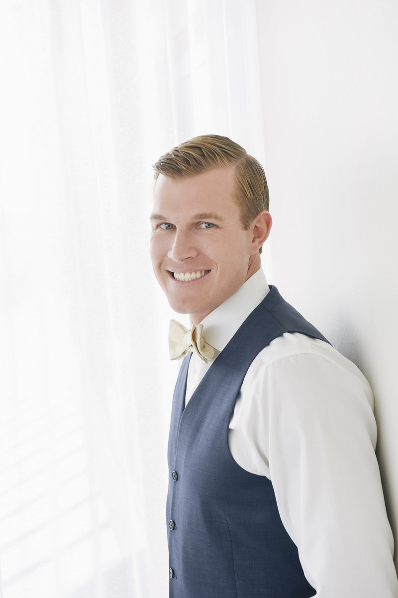 groom portrait against white wall