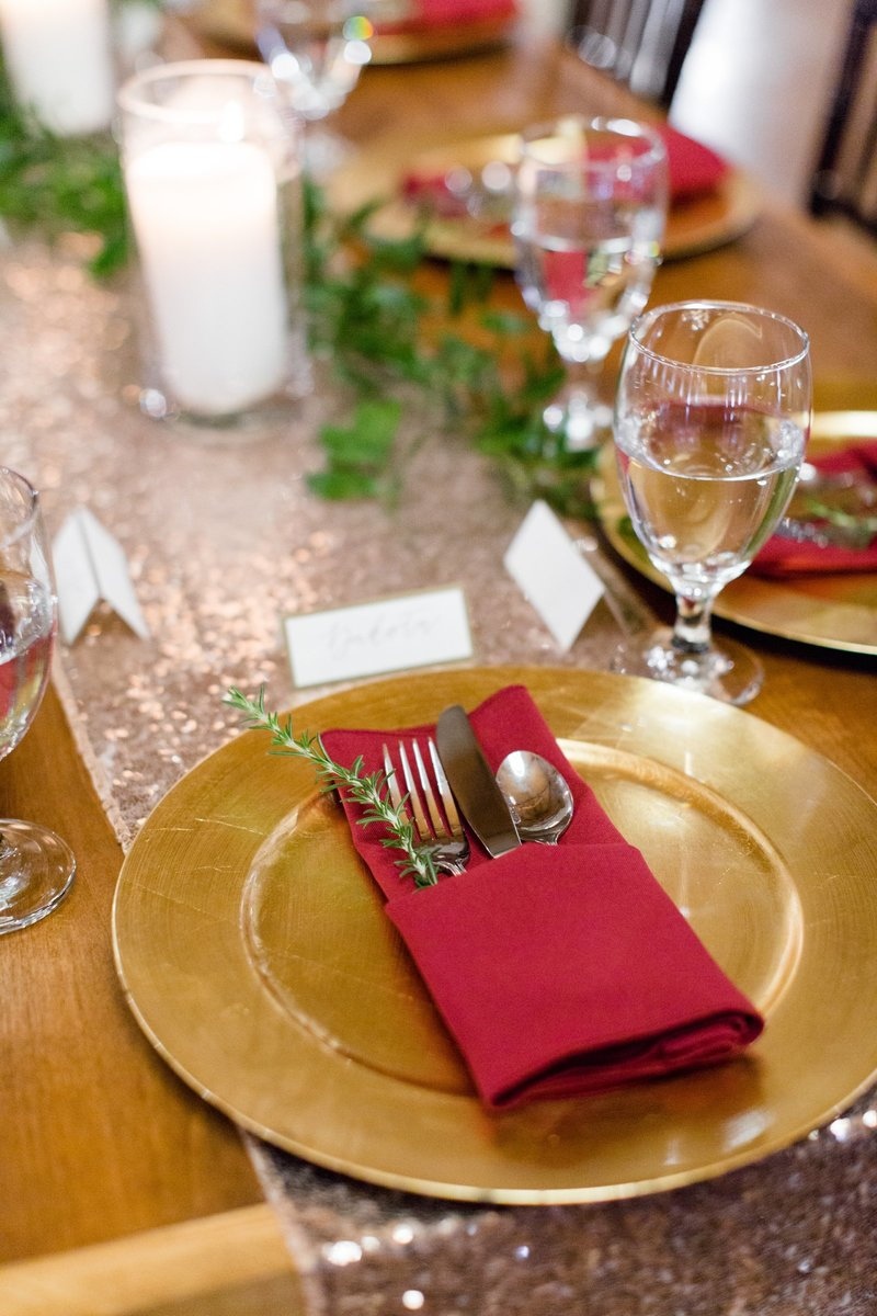 Reception table details. Winter wedding with burgundy napkins and greenery