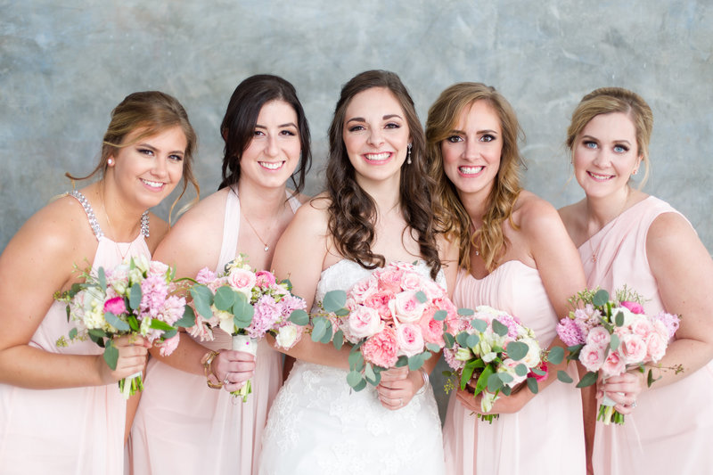 Bridesmaids in light pink dresses with bride all holding pink peony bouquets