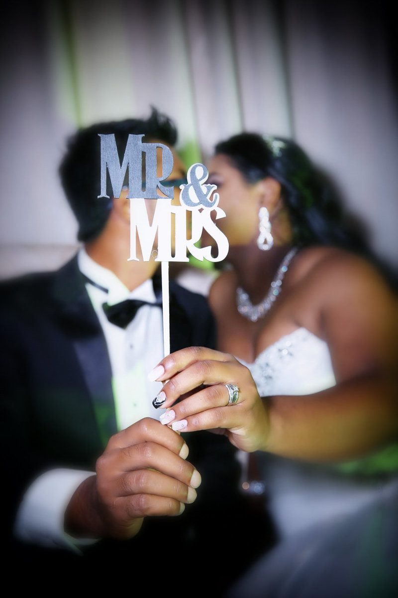 "A couple kisses behind a ""Mr&Mrs"" photo booth prop. Photo by Ross Photography, Trinidad, W.I."