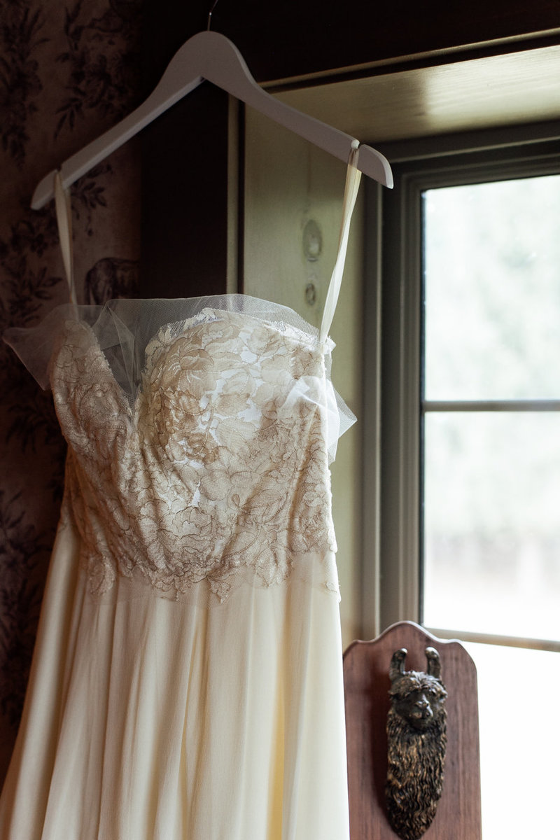 Brooklyn Bride wedding dress hanging up in barn