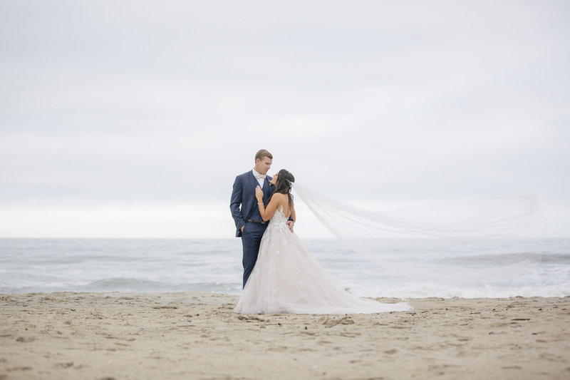 bride and groom on beach veil blowing in wind