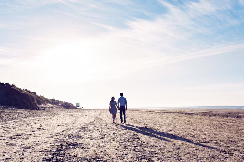 Couple walk along the beach in the spring sunshine