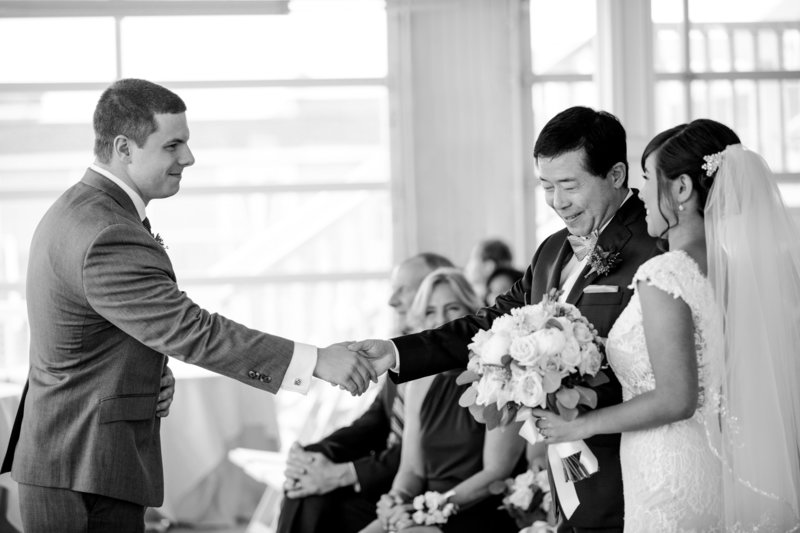 black and white father shaking hands with groom at alter