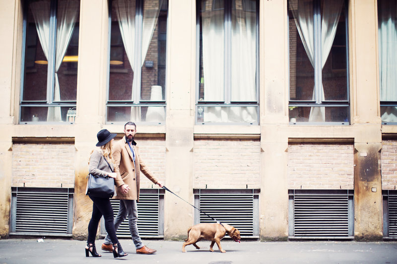 Couple walk their dog hand in hand along the city streets