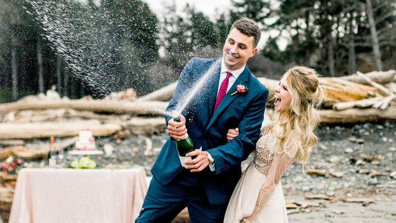 bride and groom popping champagne on the beach wedding site