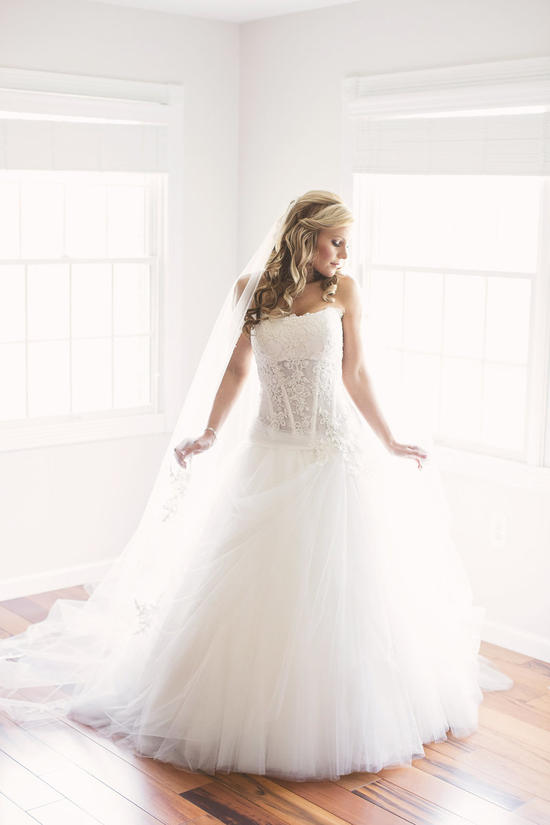 light and airy full length of bride in wedding dress looking away