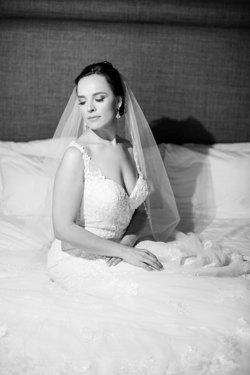 black and white bride sits on bed looking over her shoulder