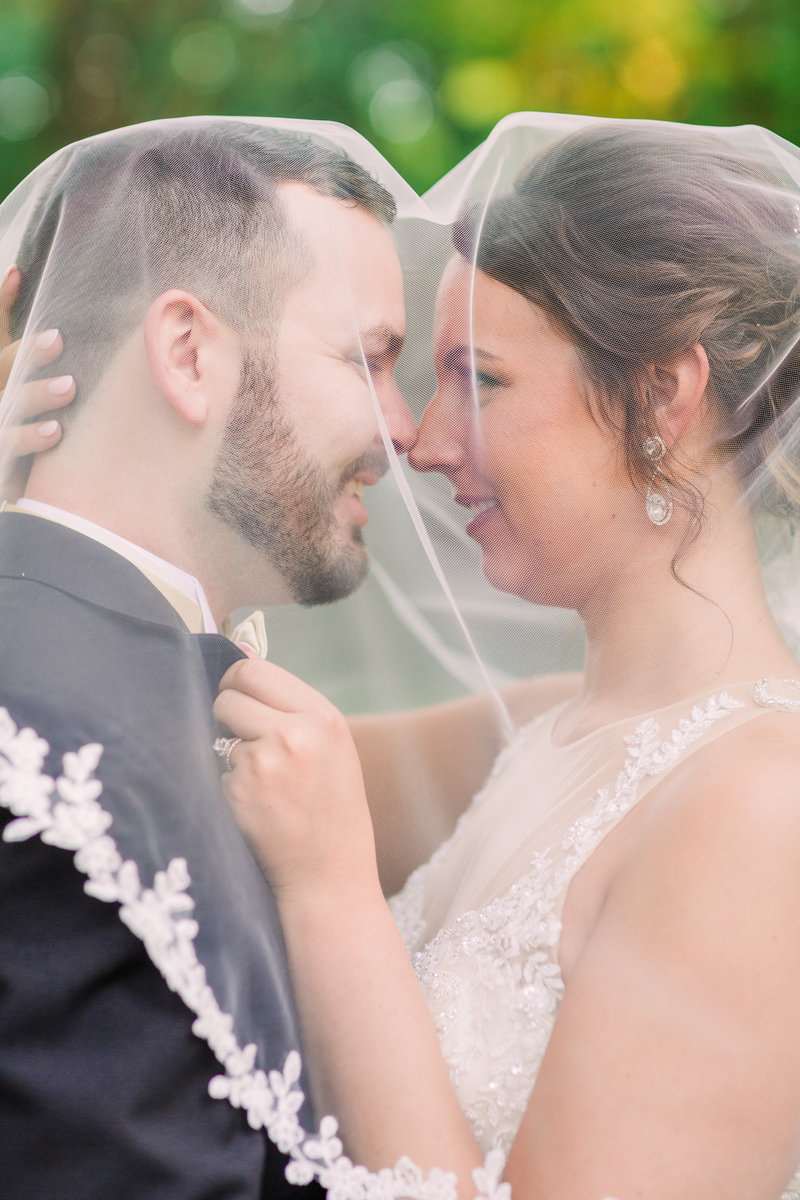 Bride and groom, Daniel and Courtney, kiss under Courtney's veil