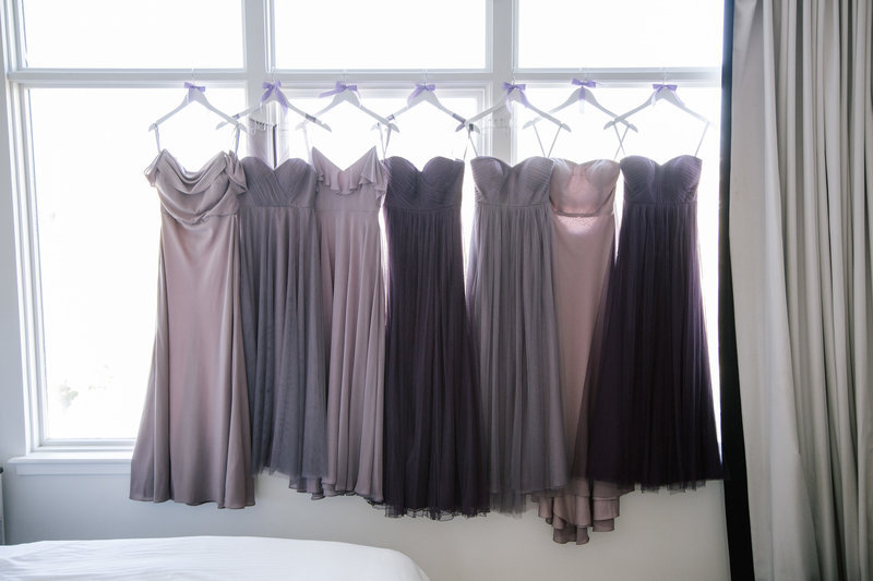 purple bridesmaids dresses hanging in hotel window