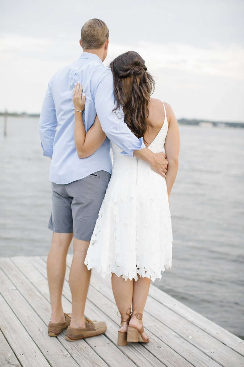 couple  with arms around each other looking away from camera at ocean from a dock