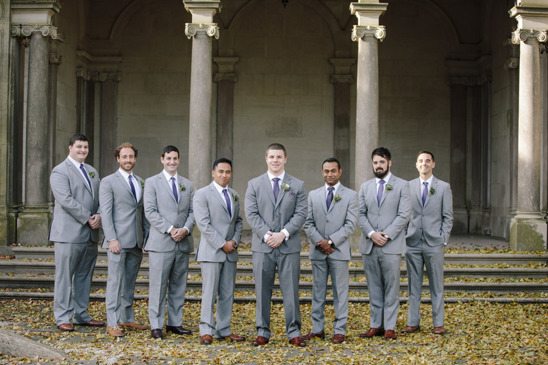 groomsmen in grey in front of large pillars at monmouth university