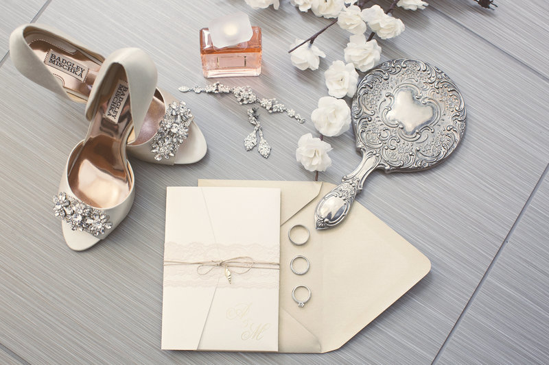 wedding invitations shoes and jewelry on grey tile