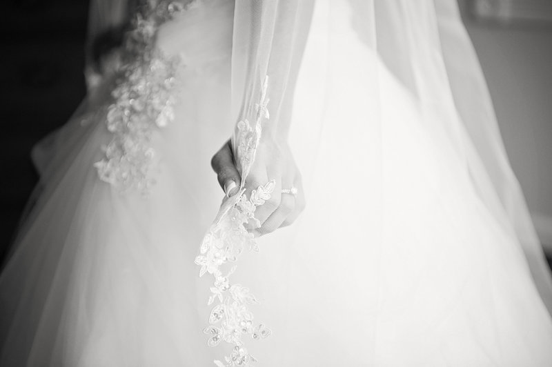 black and white bride holding her veil