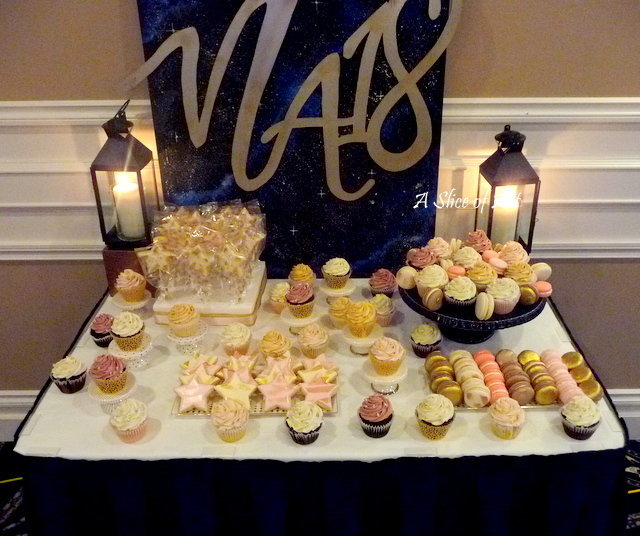 dessert table of macarons, cupcakes and sugar cookies