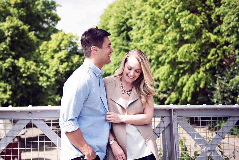 Newly engaged couple laugh on the bridge over the river Dee in Chester