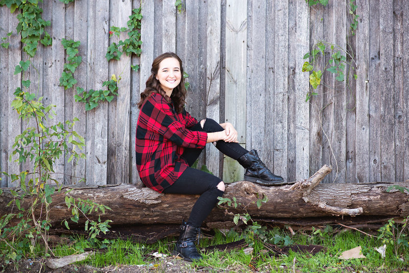 Senior portrait wearing red and black plaid shirt sitting on a log in an alley in the Bishop Arts District Dallas