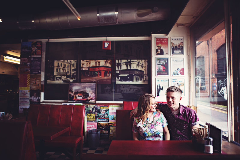 A couple sit in a retro cafe sharing a moment