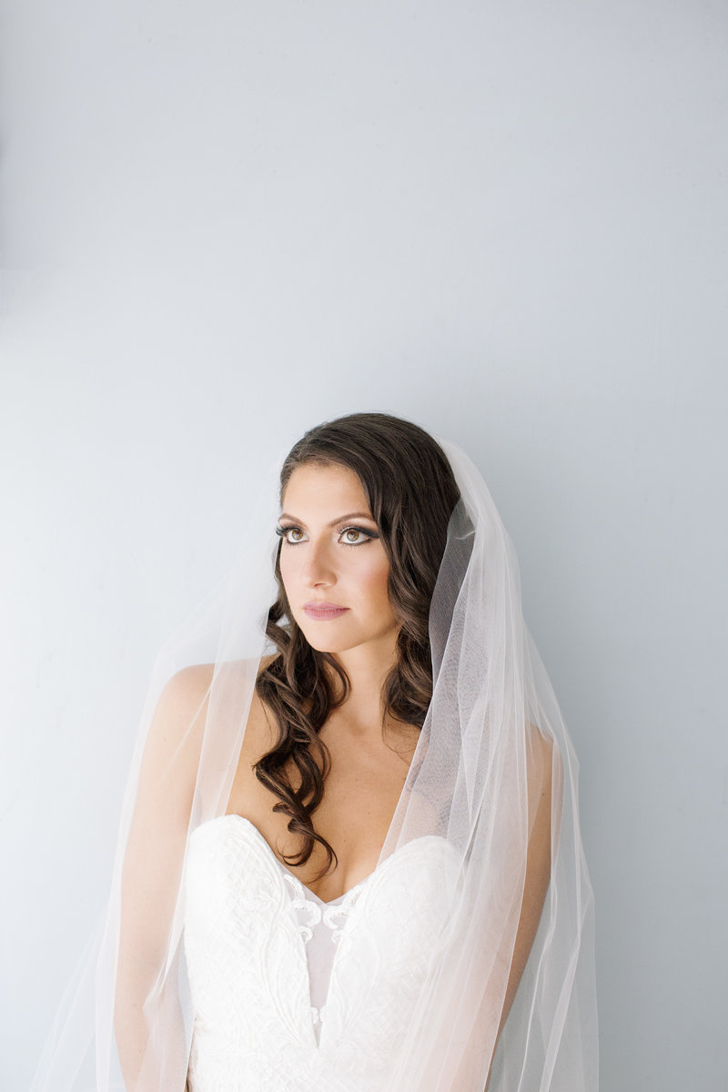 bride with veil stands in front of blue wall