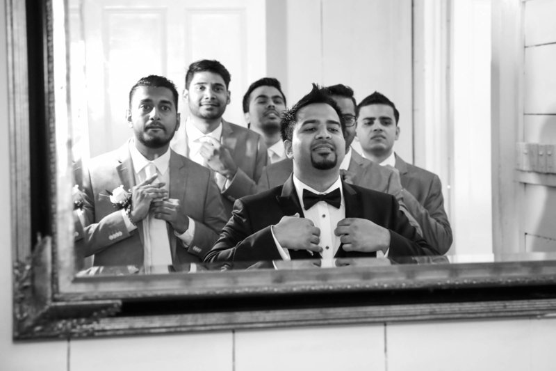 B+W image of groom and groomsmen adjust their suits in a mirror. Photo by Ross Photography, Trinidad, W.I..