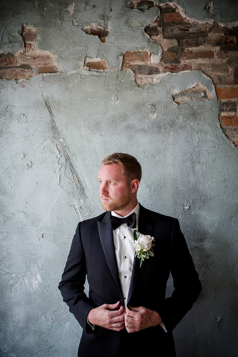 Groom in front of brick and blue wall at Houston Station Wedding Venue by Knoxville Wedding Photographer, Amanda May Photos.