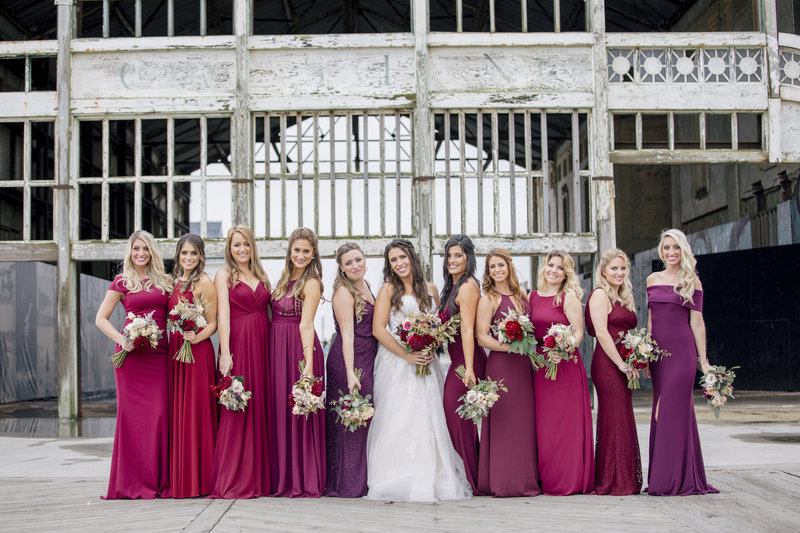 bridesmaids wearing maroon  relaxed at asbury park boardwalk