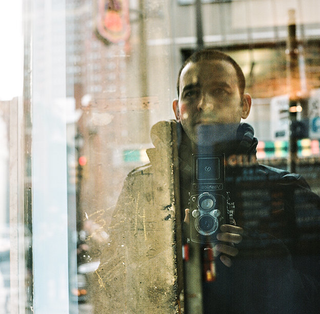 A film portrait of russ hickman photography in the reflection of a window in philadelphia, pa.