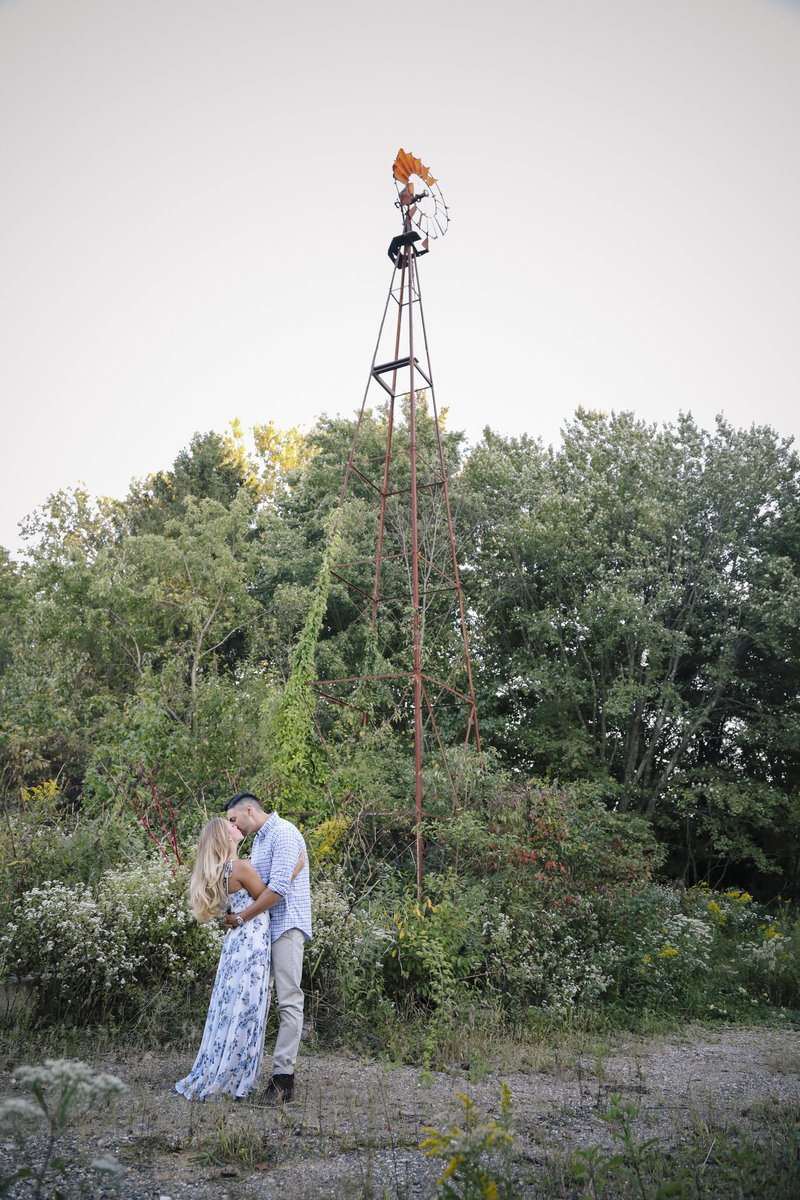 couple kissing in front of old weather vane at winery