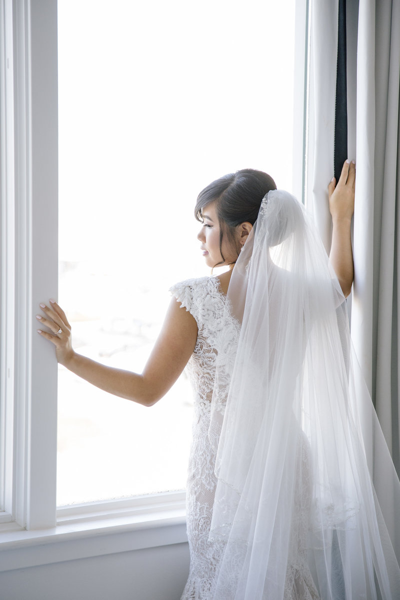 bride stands in front of window and white wall