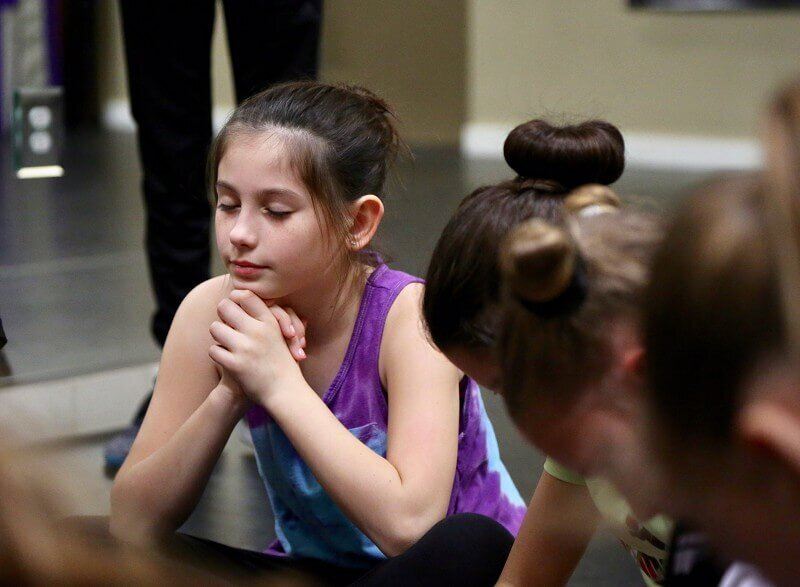 Performer praying during dance class at Dallas studio