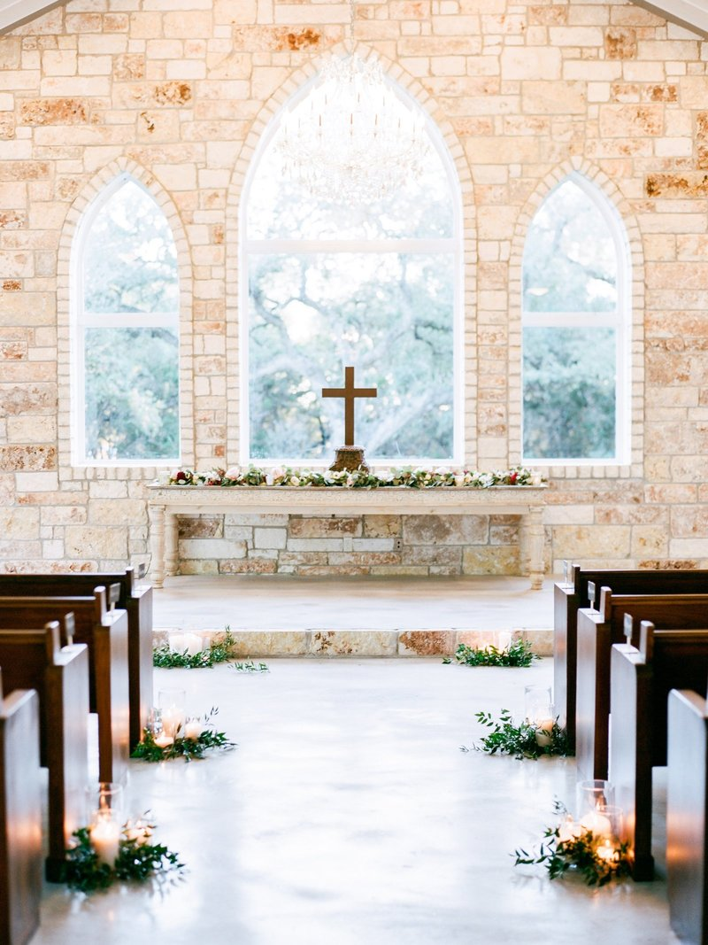 White outdoor chapel in Texas with candles lining ceremony aisle