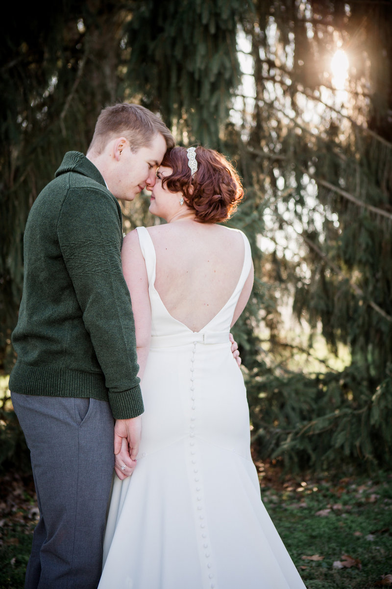 Back of bride's dress forehead to forehead with groom with light coming through evergreen trees at Shaker Village Wedding Venue by Knoxville Wedding Photographer, Amanda May Photos.