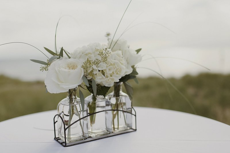 white floral centerpiece on cocktail table on beach