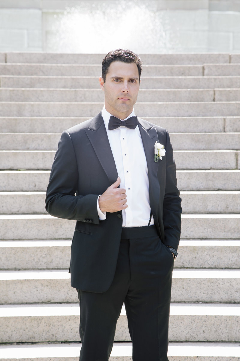 groom holding coat stands on outside grand staircase