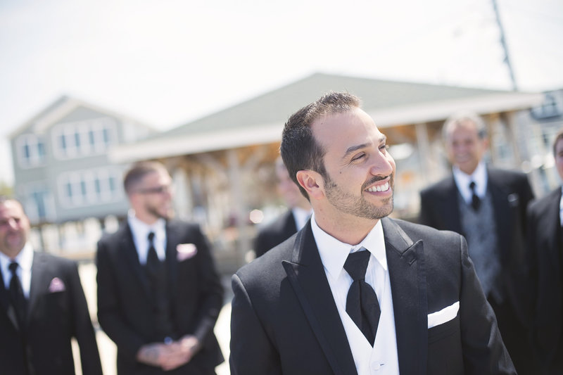 candid photo of groom walking with groomsmen behind him