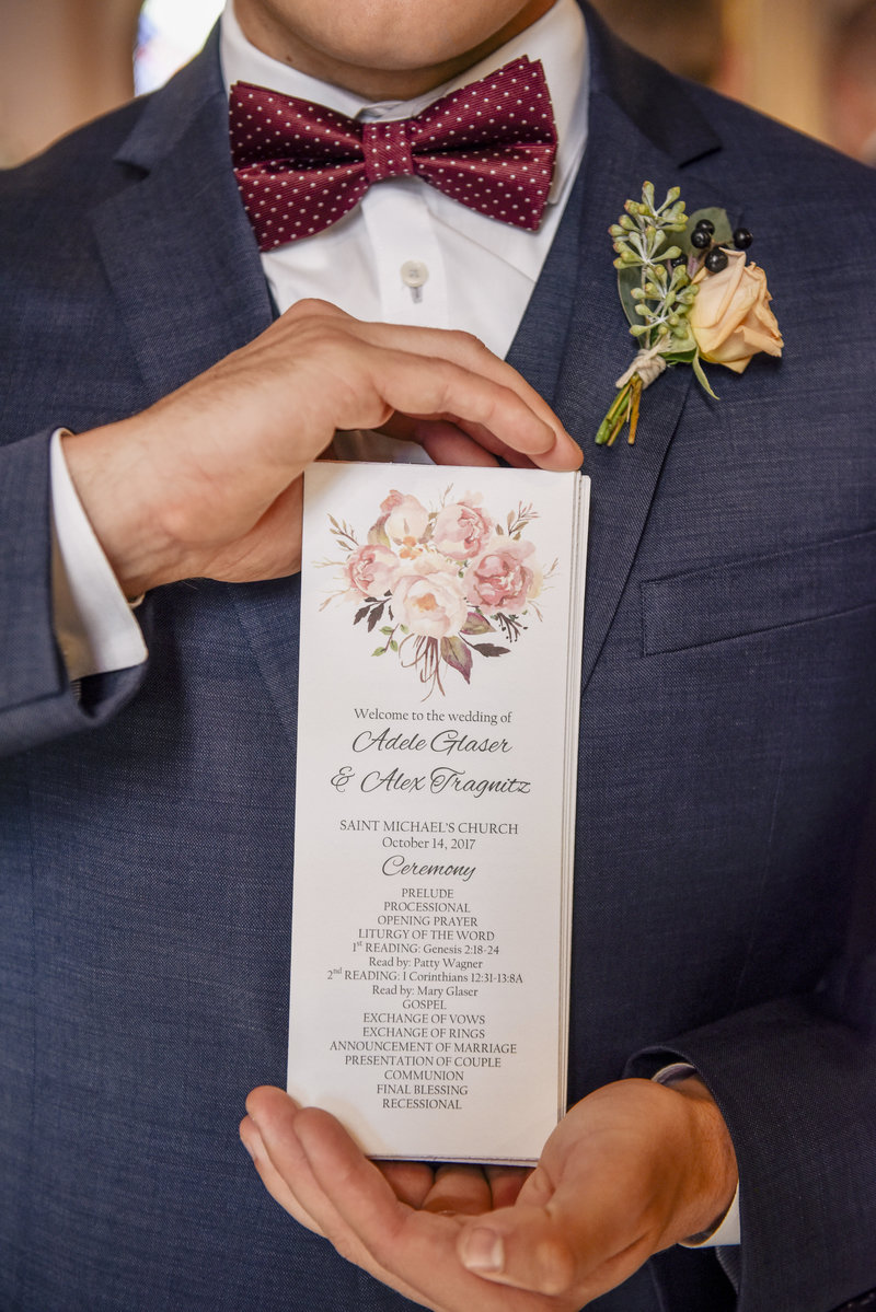 groomsman holds up wedding ceremony program
