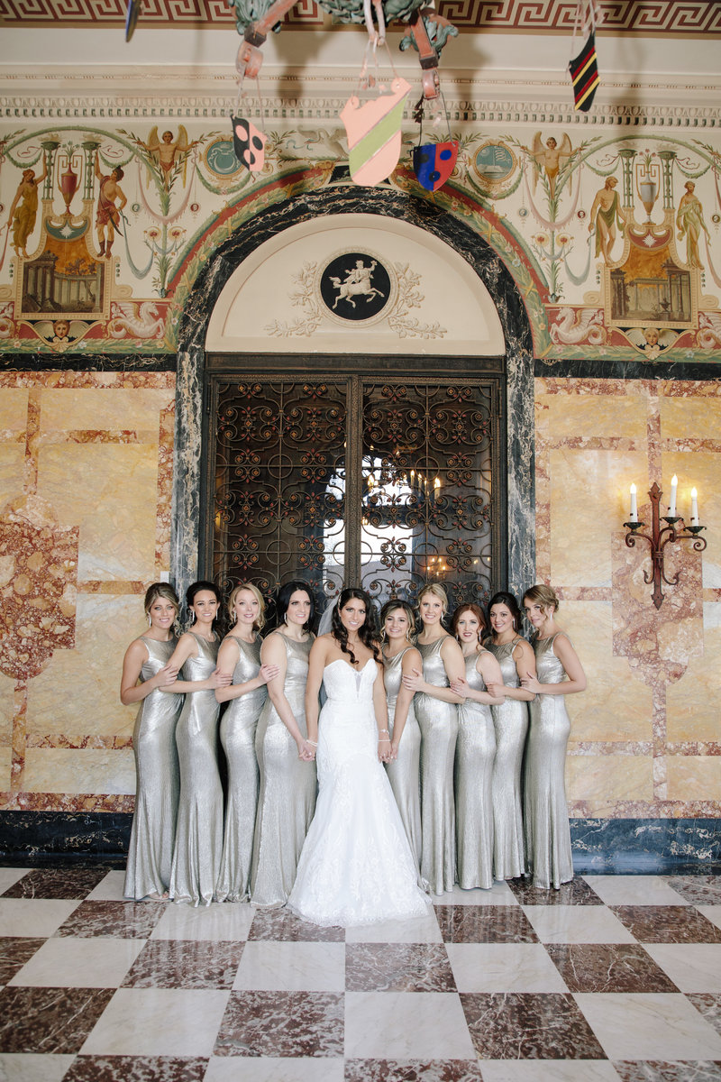 bridesmaids and bride holding hands in hall