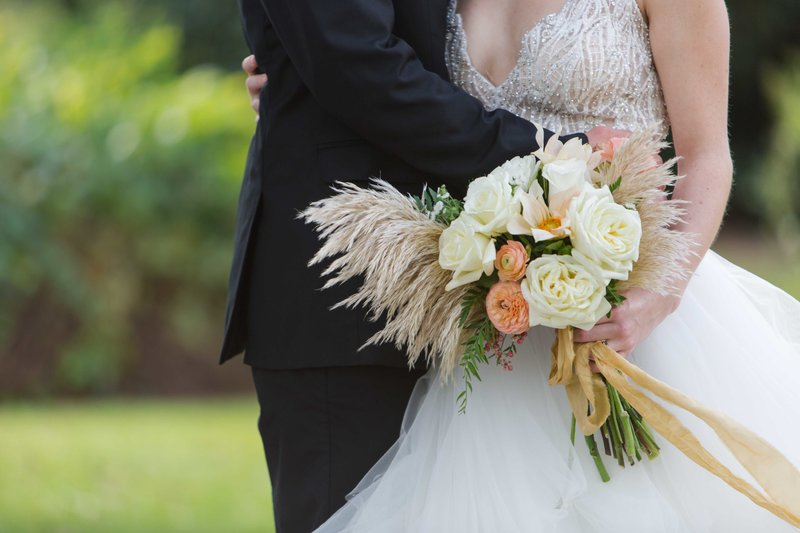Great Gatsby inspired wedding couple embrace with bouquet at Parterre