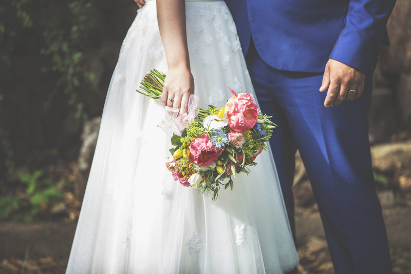 Portrait of bride and grooms hands with bouquet at a wedding in Norfolk