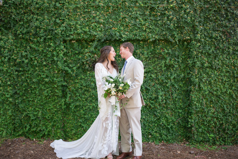 boho bride and groom laughing in front of ivy wall