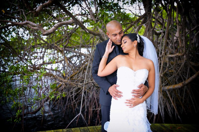 Bride enjoys groom's embrace from behind. Photo by Ross Photography, Trinidad, W.I..