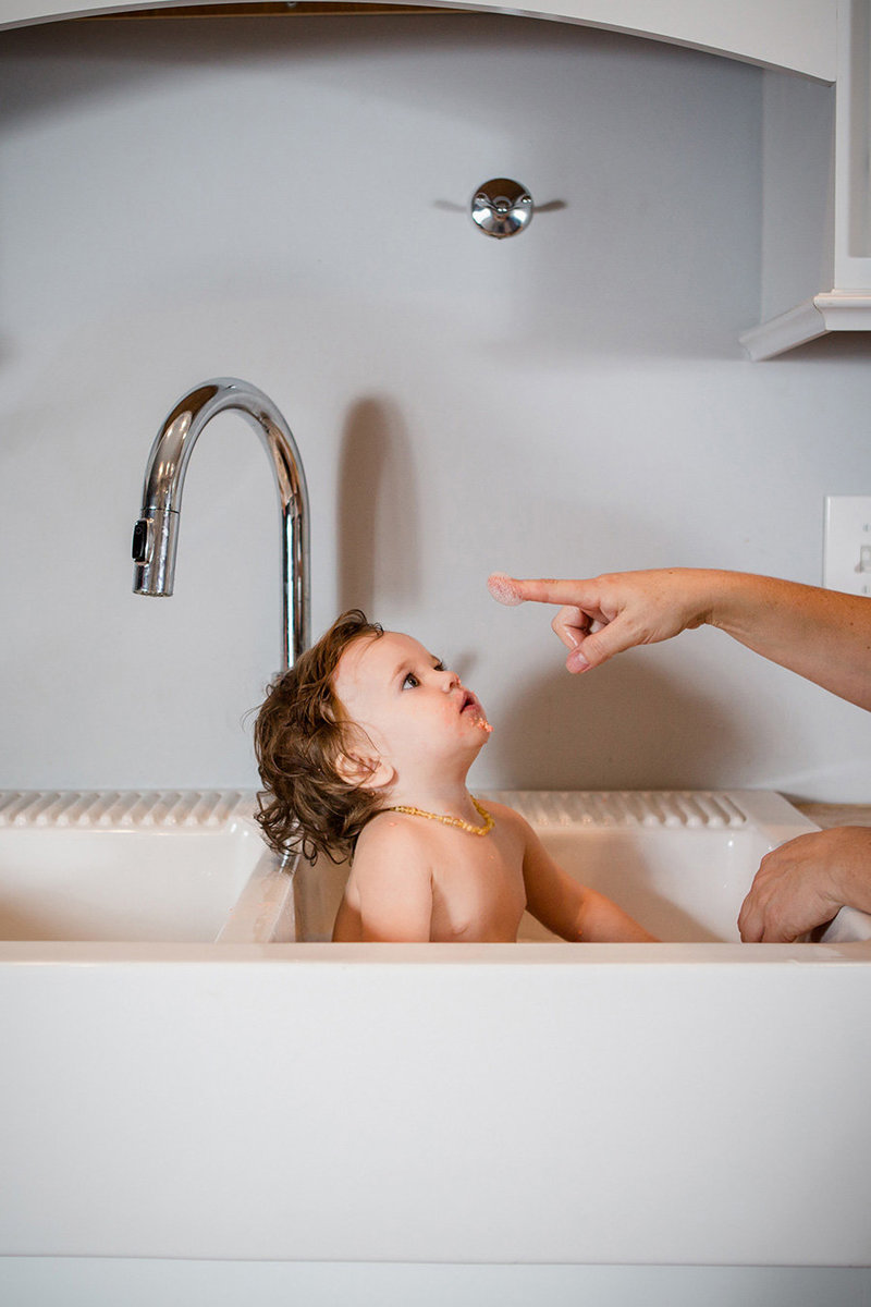 Little girl takes a bubble bath in a farm house sink by Knoxville Wedding Photographer, Amanda May Photos.