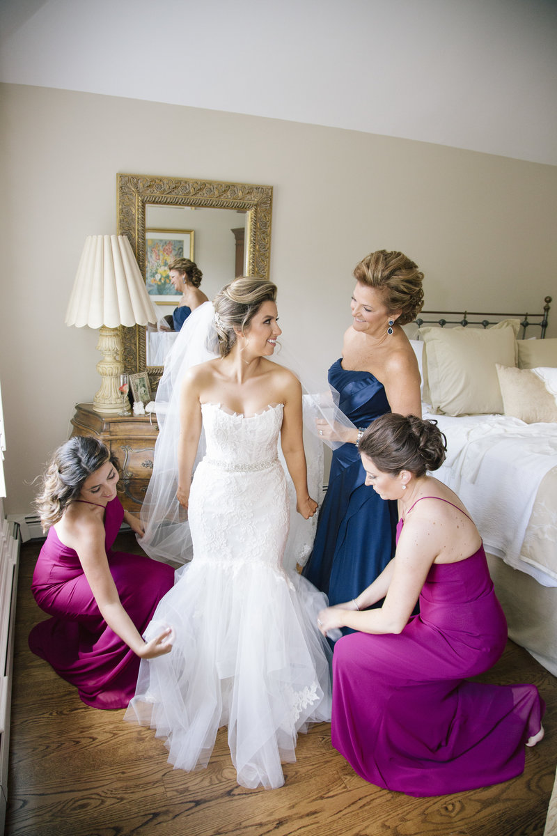 bridesmaids and mother help bride into dress