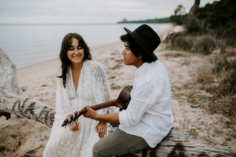 Pensacola Wedding Photographer man and woman playing guitar on the beach